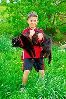 Boy carrying Turkish Angora Cat, harness, leash