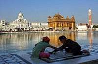 India, Penjab, Amritsar, Harmandir Sahib Golden Temple, at the edge of the sacred pool, two children play at labyrinth game
