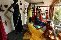 India, window dresser in a fabric shop for saris
