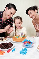 Girl blowing out birthday candle with their parents
