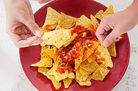Close_up of two people´s hands picking nachos from a platter