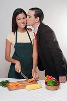 Man kissing a woman cutting vegetables