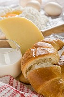 Close_up of a croissant with milk and a slice of cheese