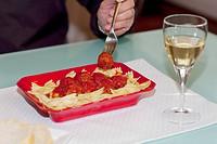 Man eating farfalle pasta and meatballs