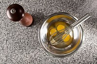 Egg yolk with a wire whisk in a bowl next to a pepper mill