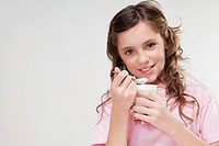 Portrait of a girl eating yogurt from a cup