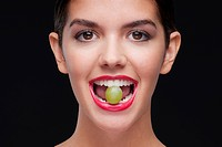 Woman holding a green grape between her teeth