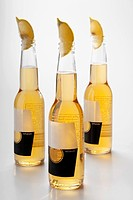 Close_up of lemon wedges in beer bottles