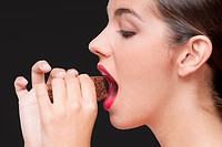 Side profile of a woman eating a brownie