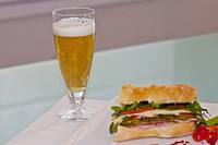 Close_up of a sandwich with a glass of beer