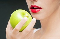 Close_up of a woman holding a granny smith apple