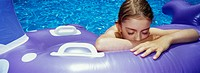 Girl 8_9 with eyes closed floating on inflatable in swimming pool