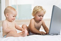 Two babies 6-12 months, 12-24 months playing with laptop computer (thumbnail)