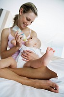 Young mother feeding baby 6_12 months on bed with baby bottle