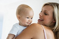 Young mother holding baby 6_12 months, baby looking over shoulder, smiling
