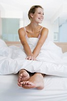 Young woman sitting on bed, smiling, feet sticking out from under bedcover