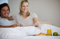 Young couple sitting on bed, smiling, breakfast in front of them