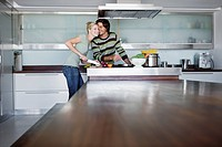 Young couple in modern kitchen, cooking together, kissing, smiling