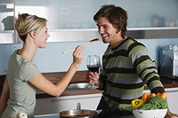 Young couple in modern kitchen, cooking, drinking red wine, tasting food