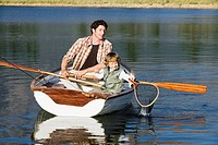 Father and son 4_7 in rowing boat with fishing net, on lake