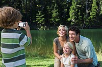 Boy photographing family outdoors, mother, father and sister posing for picture (thumbnail)
