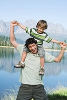 Father carrying son 4-7 on his shoulders, outdoors, lake in background (thumbnail)