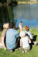 Young Family sitting on grass looking at compass and lake, outdoors