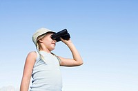 Girl 8_13 standing outdoors using binoculars