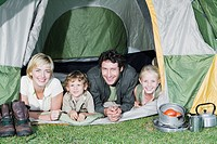 Young Family with two children camping looking out of tent, smiling