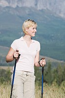 Young woman outdoors, hiking with Nordic_walking sticks