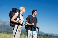 Young couple outdoors, hiking with backpack and Nordic_walking sticks