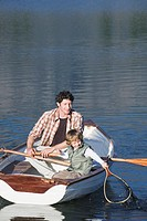 Father and son 4_7 rowing in rowing boat, on lake with fishing_net