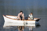 Father and son 4_7 sitting in rowing boat on lake, catching fish with rod