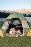 Young couple camping in tent, kissing, lake and mountains in background