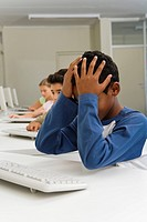School children 10_13 in computer room, boy under stress head in hands