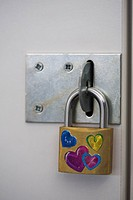 Padlock on school locker with heart stickers