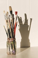 Paintbrushes in Glass jar in classroom with shadow on tiles, close_up