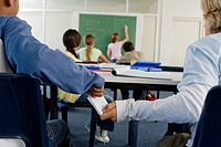 Two boys 10_13 in classroom passing piece of paper, cheating