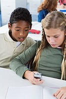 School children10-13 using mobile phone in classroom, sitting looking at phone (thumbnail)