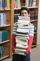 Boy 10-13 in library, straining to carry pile of school books (thumbnail)