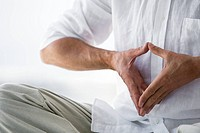 Senior man sitting, doing Yoga exercise, detail of hands indoors
