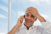 Mature man at window smiling, using cell phone, holding hand to head