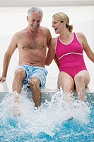 Senior couple sitting on edge of swimming pool laughing and splashing (thumbnail)