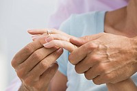 Senior couple man putting diamond ring on woman's finger, detail of hands