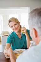Mature couple at breakfast table holding hands