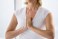 Senior woman sitting, doing Yoga exercise, detail of hands indoors