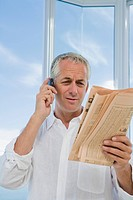 Mature man stressed, using Cell phone and reading financial newspaper