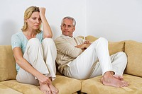 Mature couple sitting on sofa, having argument