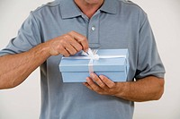 Senior man opening blue present, detail of hands