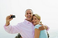 Mature couple laughing while taking self portrait with camera phone